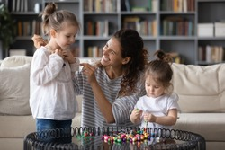 Creative young mother wearing handmade pendant on smiling cute daughter, enjoying daycare playtime with preschool girls in living room, teaching making bracelets, stringing beads on weekend at home.