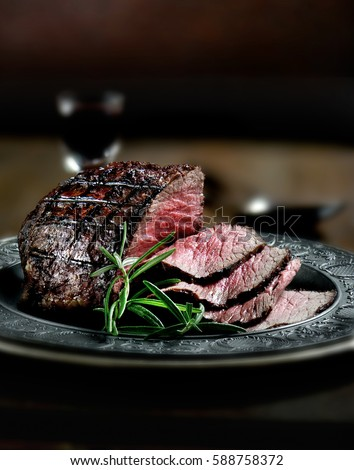 Creatively lit, fresh British roast beef sliced for serving against a dark background with rosemary herb garnish. Generous accommodation for copy space.