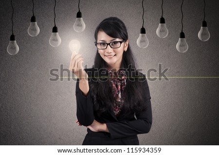 Creativity concept: Beautiful Asian Businesswoman with glasses holds a bright light bulb