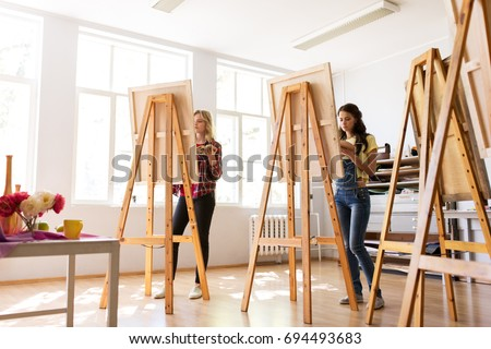 creativity, education and people concept - group of woman artists or students painting still life on easels at art school studio