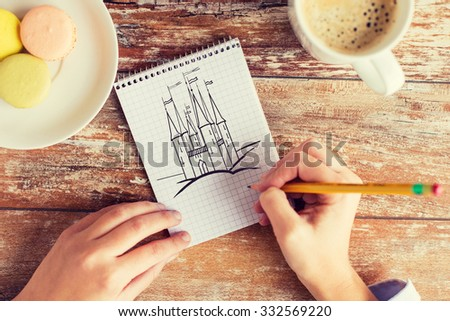 creativity, imagination, inspiration and people concept - close up of female hands drawing with pencil in notebook, coffee and cookies on table