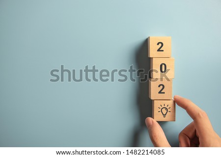 Creativity inspiration concepts, Woman hand arranging wood block with new year 2020 and lightbulb icon, planning ideas.
