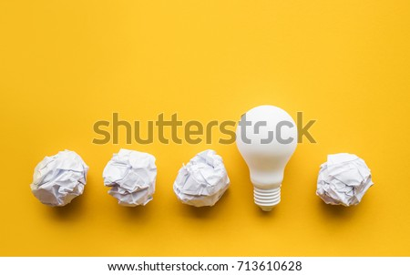 Creativity inspiration,ideas concepts with lightbulb and paper crumpled ball on pastel color background.Flat lay design.
