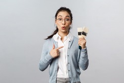 Creativity, repairs and overhaul concept. Amused and curious asian girl in glasses, holding brushes and pointing at them questiones, interested what person renovating, have repairment woks