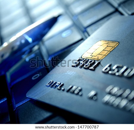 Credit card and ball pen on a laptop