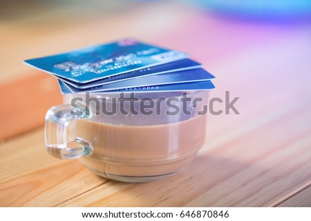 Credit card and glass of hot coffee on wooden table in the morning, soft tone. shallow focus #646870846