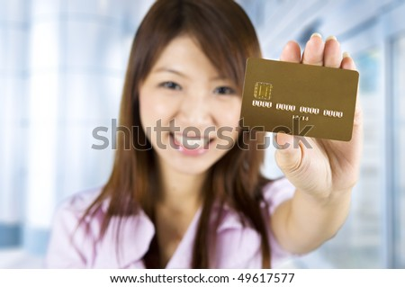 Credit card. Asian woman holding a credit card, focus on the card. Card number and expiry date created by my own.