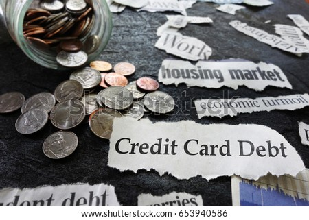 Credit Card Debt newspaper headline, with coin jar and economic news items                              #653940586
