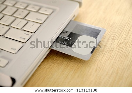 Credit card insert inside laptop on the wooden desk
