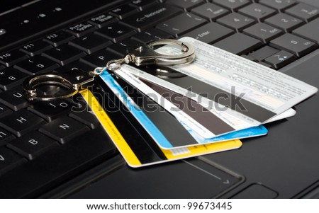 credit card of handcuffs on a computer keyboard