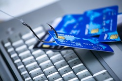Credit card phishing. Piles of credit cards with a fish hook on computer keyboard. Credit card phishing scam with credit card in fishing hook