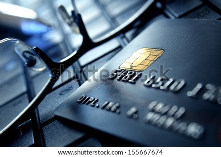 Credit card with glasses on a laptop keypad