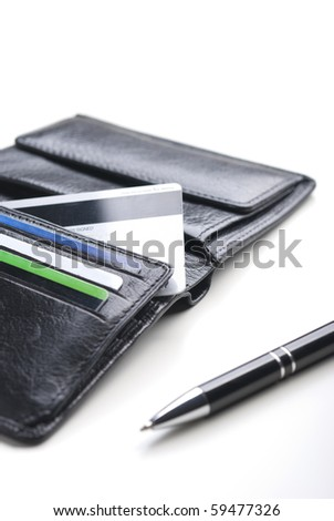 Credit cards in a black wallet and pen isolated on white background