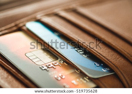 Credit cards in brown wallet in shallow focus