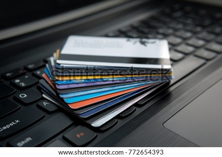 Credit cards on a laptop keyboard concept for e-commerce, consumerism or electronic banking. Internet banking. Buying goods. Payroll and a discount card for purchases in online stores.