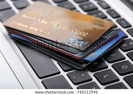 Credit cards on laptop keyboard, close up #746112946