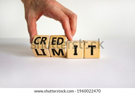 Credit limit symbol. Businessman turns wooden cubes and changes the word 'limit' to 'credit'. Beautiful white table, white background, copy space. Business and credit limit concept.