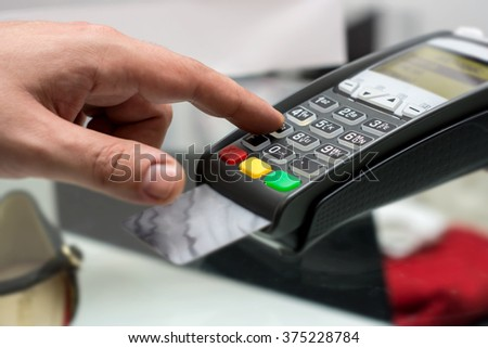 Credit or debit card password payment. Customer hand is entering pin in shop or supermarket. Payment terminal keypad, pin.  Buy and sell products and service. Close-up, selective focus.