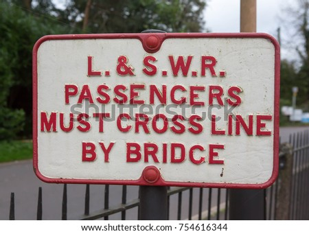 CREDITON, ENGLAND  OCTOBER 14 2017 Old London and South Western Railway sign in structing passengers to cross the line by the bridge