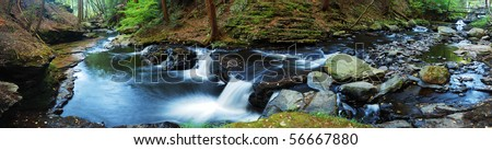 Creek panorama with wood bridge and hiking trail in woods in autumn with rocks and foliage.