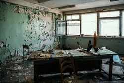 Creepy abandoned office room inside with old wooden table and windows. Horror concept