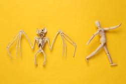 Creepy bat skeleton and running puppet on yellow background. Halloween layout