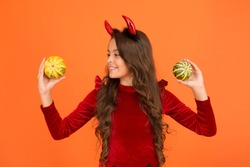 Creepy crawly. Happy little girl hold pumpkins orange background. Small child dressed up as creepy devil. Creepy look will freak out all your friends. Creepy and scary. Halloween celebration.