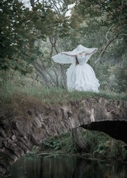 Creepy dead bride standing on the bridge outdoor. Halloween scene