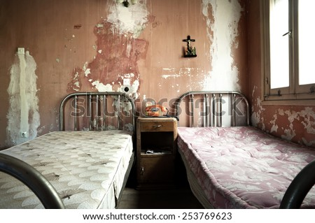 Creepy dirty and abandoned bedroom with cracked walls