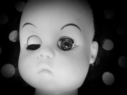 creepy doll looking by one eye in highcontrast black and white