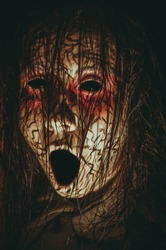 Creepy girl with black eyes opened mouth and cracked skin close-up portrait. Spooky demonic creature from hell
