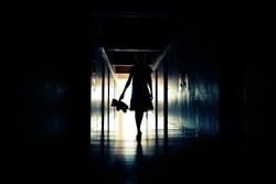 Creepy hallway with the little girl. Dark otherworldly personality. Light in a dark long corridor. The Ghost of a little girl in the house. A Ghost scares people.
