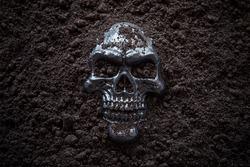 Creepy human skull in black soil