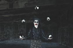 creepy hypnotic juggler clown play with balls