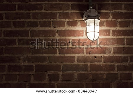Creepy light bulb on textured red brick wall