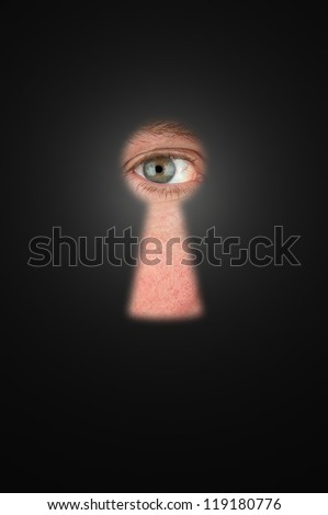 Creepy man peeking through a keyhole with focus on his eyeball.
