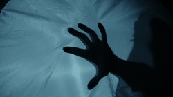 Creepy night scene: A woman's silhouette behind the fabric, a hand suddenly hits the fabric, causing terror and fear