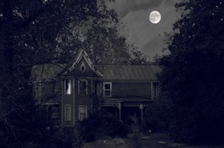 Creepy old house in black and white hidden in the forest with a full moon background and a possible ghost in the upstairs window
