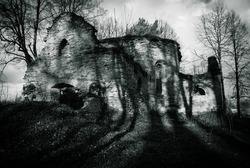 Creepy ruins of a medieval church with long, evening shadows cast by the trees. Gothic atmosphere from Eastern Europe.
