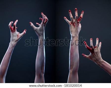 Creepy set of bloody zombie hands, studio shot over gray background