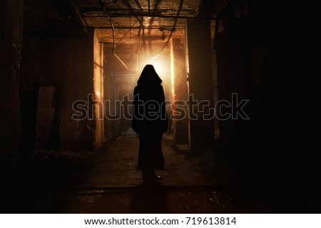 Creepy silhouette in the dark abandoned building. Horror about maniac concept