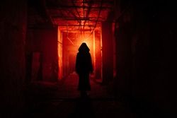 Creepy silhouette in the dark red illuminated abandoned building. Horror about maniac concept