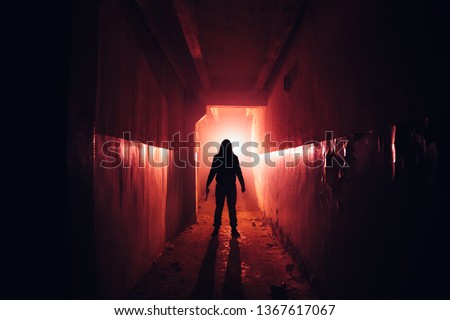 Creepy silhouette with knife in the dark red illuminated abandoned building. Horror about maniac concept. Сток-фото ©