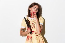 Creepy zombie woman covered in blood stains holding a knife and looking at camera isolated over white background
