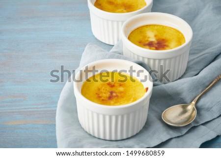 Crema catalana, Spanish dessert in three ramekin on blue table, copy space, side view Foto d'archivio ©