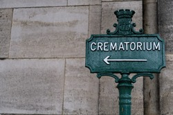 Crematorium. Inscription on a metal panel. Cemetery path.