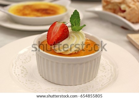 Creme Brulee  served with cream, strawberry and mint leaf  #654855805