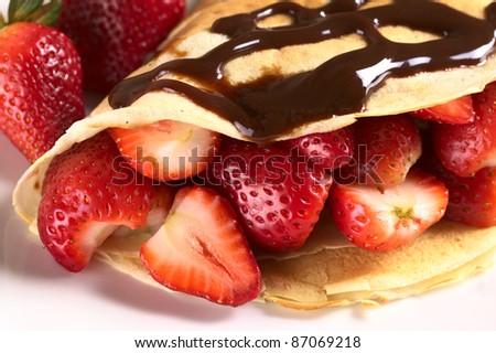 Crepe filled with fresh strawberries and chocolate sauce on top (Selective Focus, Focus on the strawberry cut on the left and the front of the two strawberries beside)