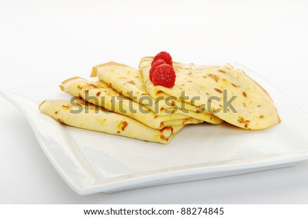 Crepe on a plate with a raspberry. A detailed photo fried thin pancake.Isolated on white - stock photo