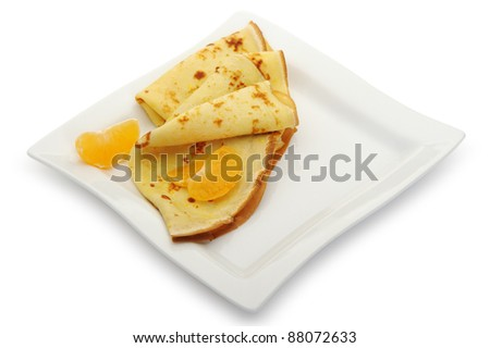 Crepe on a plate with mandarin. It is isolated on a white background. A detailed photo fried thin pancake.